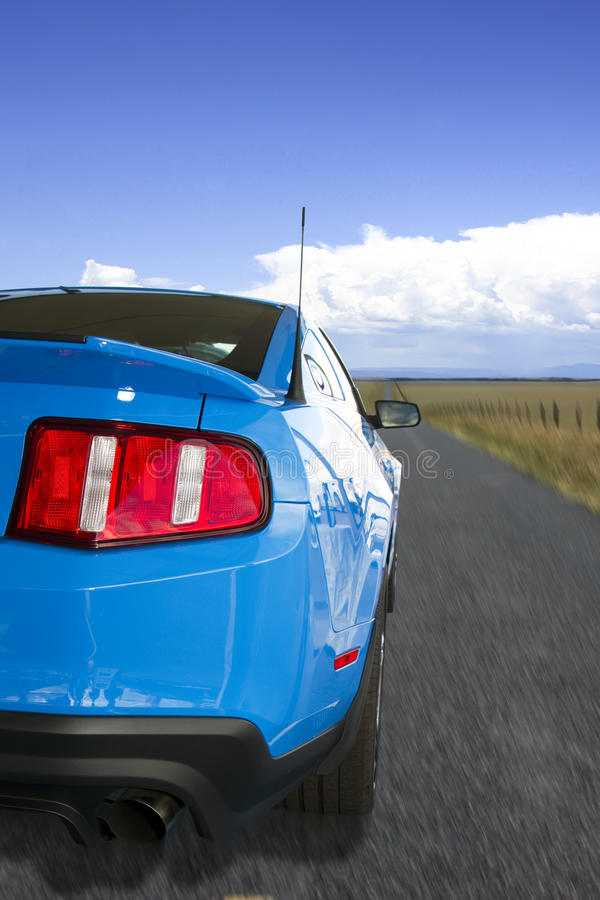 Blue American Sports Car On The Open Road. Brand new metallic blue American sports car on the open road royalty free stock photo
