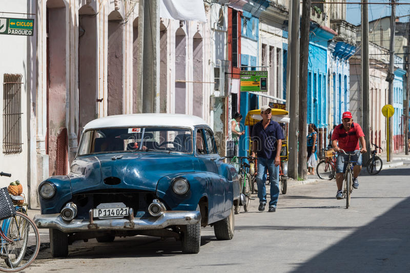 Blue american vintage car in the province Villa Clara with street life view stock photo
