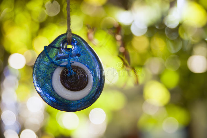 Blue amulet hanging on a tree. stock images
