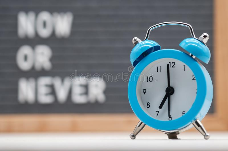 blue analog alarm clock on English text background now or never stock photos