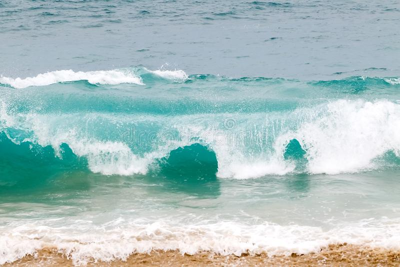 Blue and aquamarine color sea waves and yellow sand  with white foam. Marine beach background. royalty free stock photography