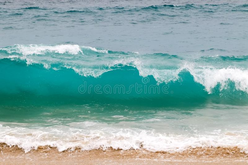 Blue and aquamarine color sea waves and yellow sand  with white foam. Marine beach background. stock image