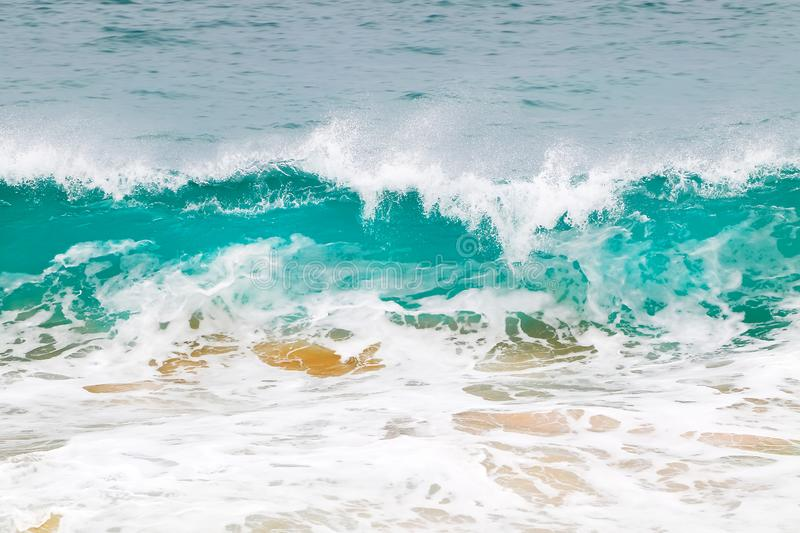 Blue and aquamarine color sea waves and yellow sand  with white foam. Marine beach background. stock photo