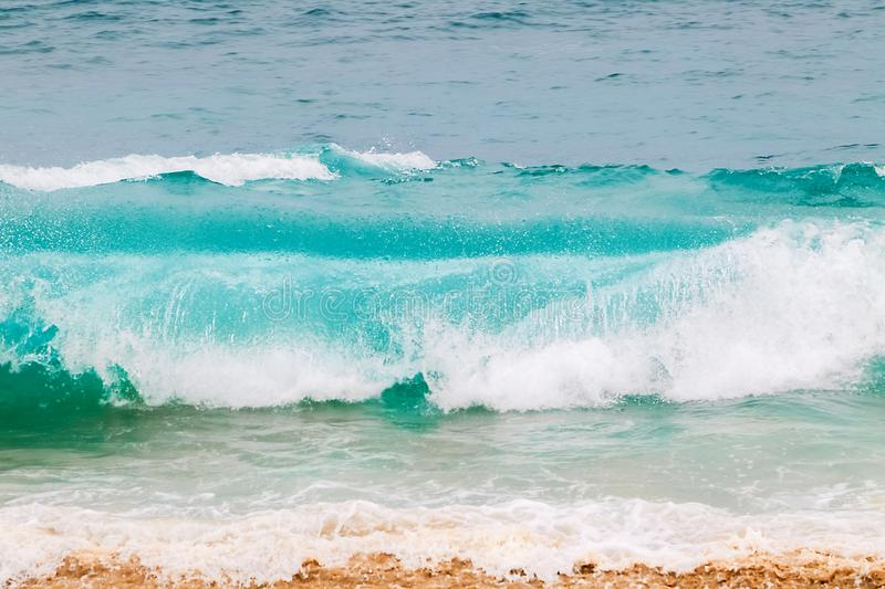 Blue and aquamarine color sea waves and yellow sand  with white foam. Marine beach background. royalty free stock photos