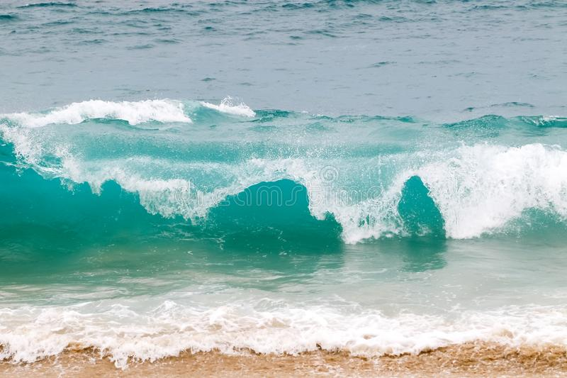 Blue and aquamarine color sea waves and yellow sand  with white foam. Marine beach background. royalty free stock photo