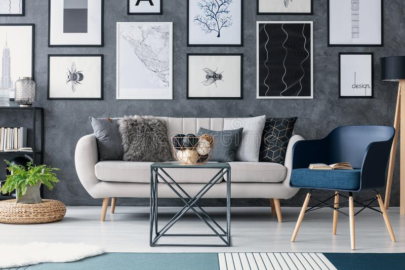 Blue armchair next to sofa and table in living room interior with posters and plant on pouf. Real photo stock photos
