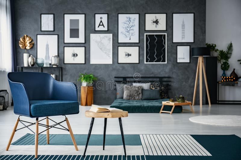Blue armchair next to wooden table in spacious living room interior with gallery and lamp. Real photo with blurred background stock photography