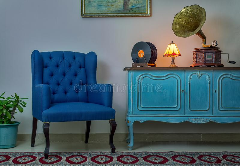 Blue armchair, vintage wooden light blue sideboard, lighted antique table lamp, old phonograph gramophone and vinyl records royalty free stock photo