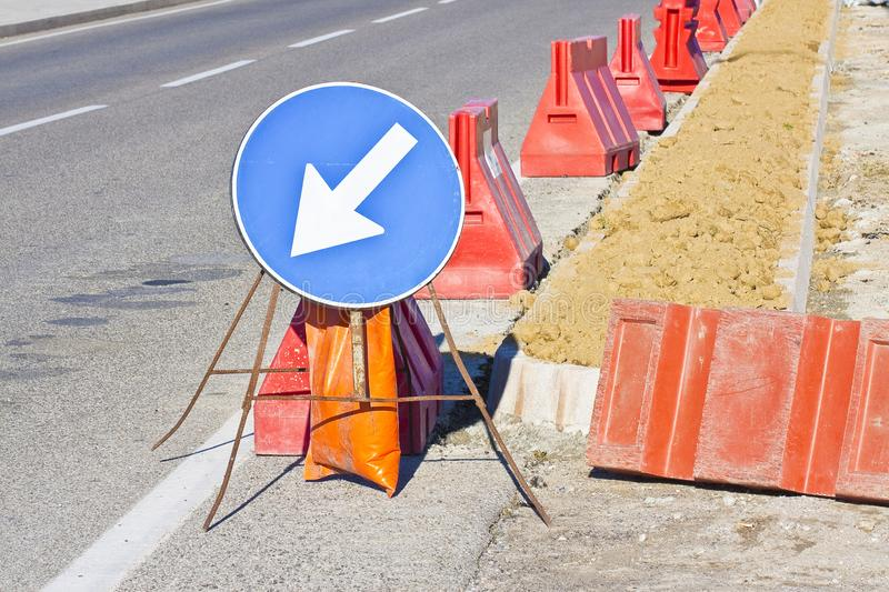 Blue arrow sign in a construction site for street works stock image