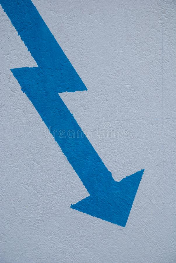 Blue arrow tilted in vertical. On white background painted on wall stock photos