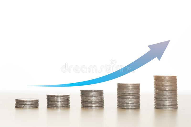 Blue arrow on top stack of coins white background. Blue arrow on top stack of coins white background, Money business concept royalty free stock photo