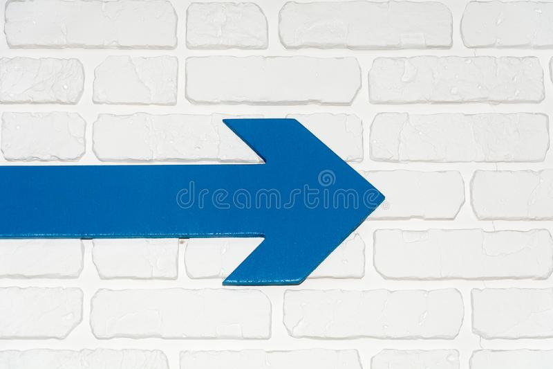 Blue arrow on a white brick wall royalty free stock photography