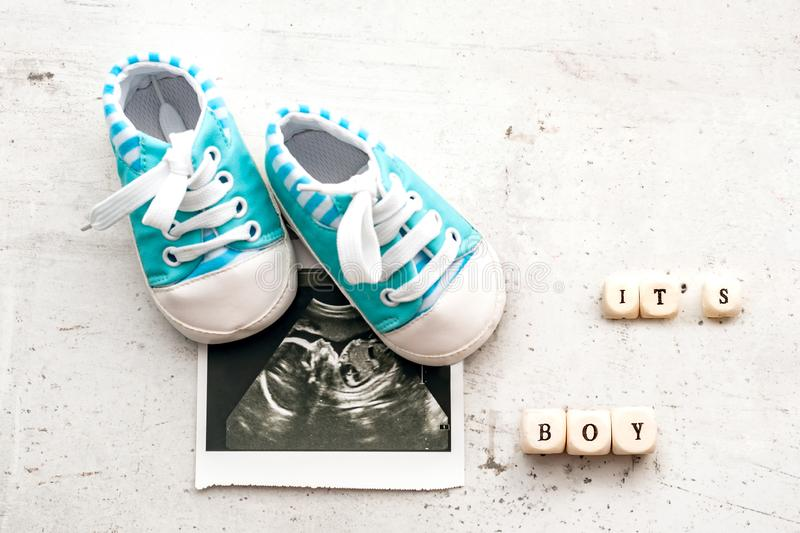 Blue baby booties with a picture of ultrasound for 20 weeks on a light background. Inscription its boy. royalty free stock image