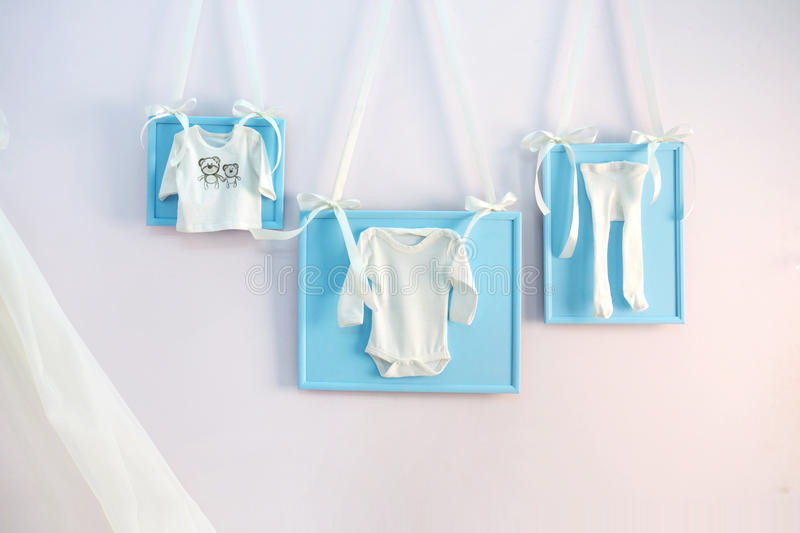 Blue baby clothes on the clothesline ribbons on the wall. Baby party stock photos