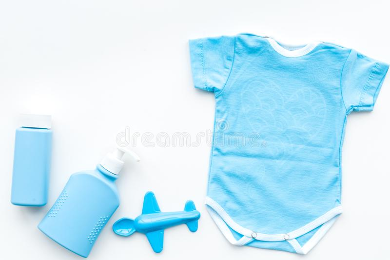 Blue baby clothes for little boy. Bodysuit, toys, cosmetics on white background top view copy space royalty free stock image
