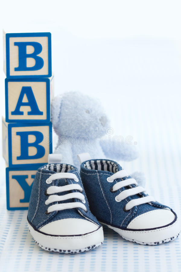 Blue baby shoes. Blue denim baby shoes, baby blocks and teddy bear royalty free stock photo