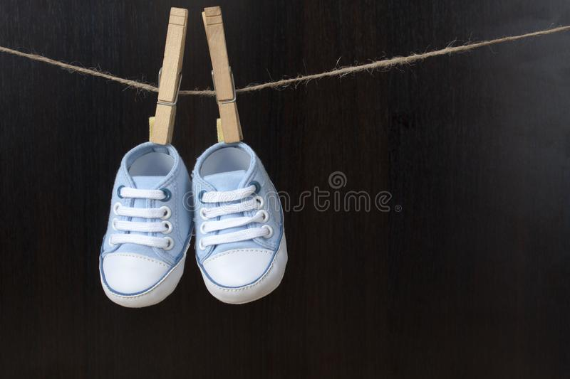 Blue baby sneakers hung with clamps on a string royalty free stock image