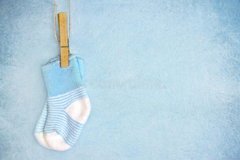 Blue baby socks on a textured background stock photo