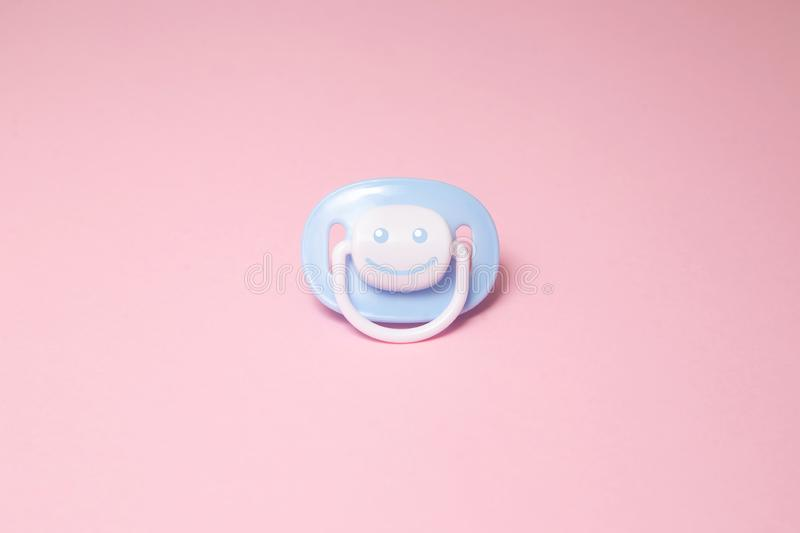 Blue baby soother or dummy with a smile on a pink background with copy space. Baby care, orthodontist, children sleep, newborn, stock photos