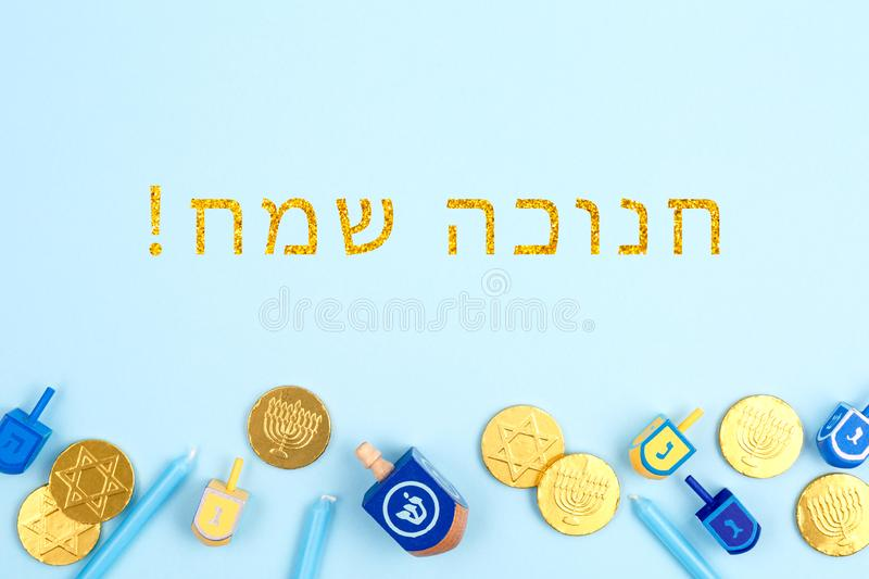 Blue background with multicolor dreidels, menora candles and chocolate coins with Happy Hanukkah wording in Hebrew royalty free stock images