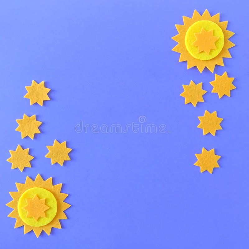 Blue Background with Yellow Stars and Copy Space. Blue background with copy space and yellow felt star ornaments, handmade crafting felt toy for children royalty free stock photo