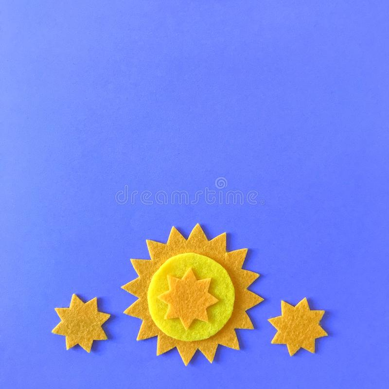 Blue Background with Yellow Stars and Copy Space. Blue background with copy space and yellow felt star ornaments, handmade crafting felt toy for children stock photos