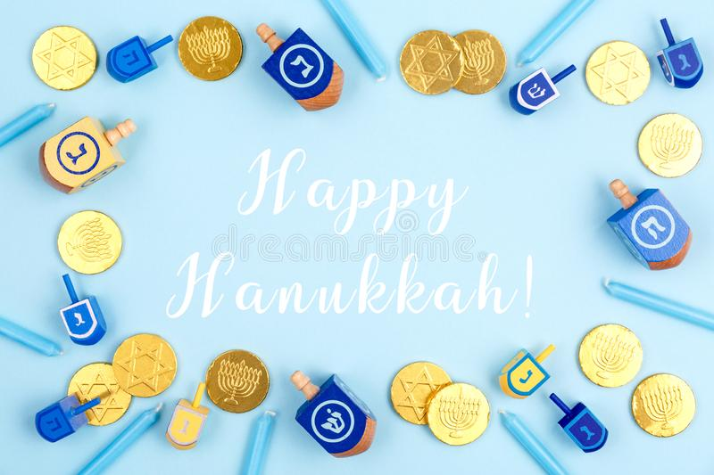 Blue background with dreidels, menora candles and chocolate coins with Happy Hanukkah wording. Hanukkah and judaic holiday concept. Horizontal royalty free stock photography