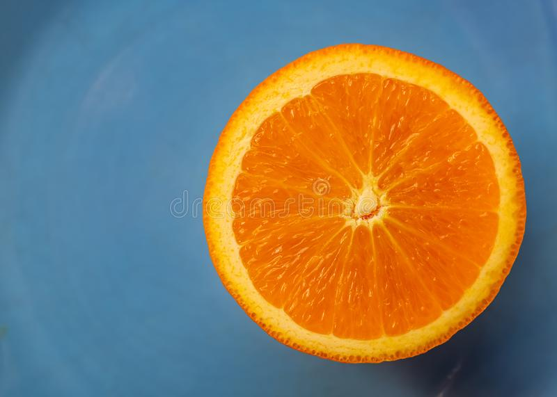 Blue background with fruit citrus an orange or half  tangerine. Macro image and close-up, concept for healthy food. Top view. Soft focus. Copy space royalty free stock photos