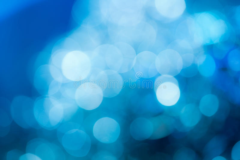 Blue background. Blue holiday party background. Abstract with bright twinkles, sparkles, blurred, defocused light stock photography