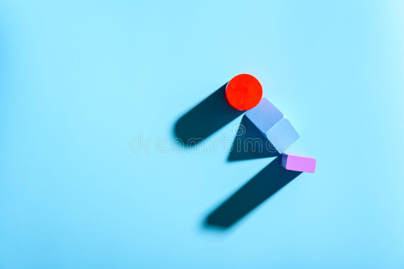 Blue background with red geometric figures casting shadows in a simple composition.  stock photography