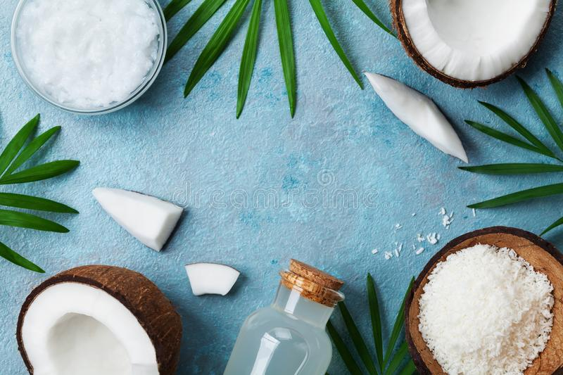 Blue background with set of organic coconut products for spa treatment, cosmetic or food ingredients. Oil, water and shavings. royalty free stock photos