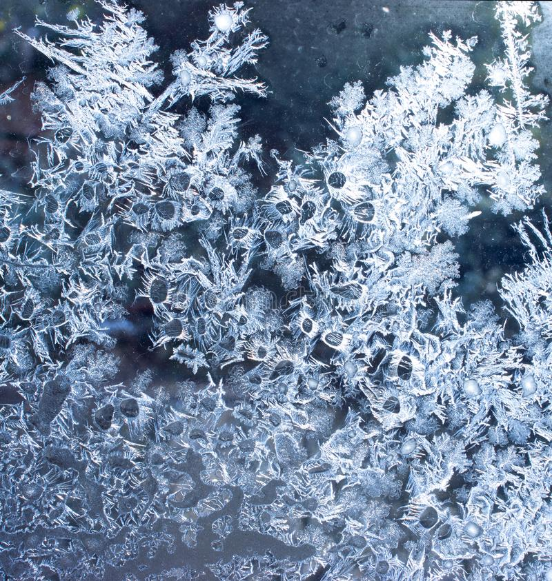 Blue background with silver frost on the window. Frozen water. On the window creates silver beautiful decoration ornaments stock photos