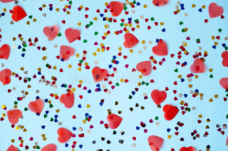 Blue background with small multicolored and big red hearts royalty free stock photography