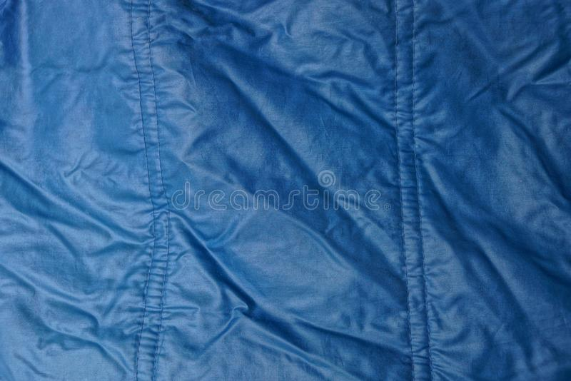 Blue texture of synthetic fabric from a fragment of crumpled clothes. Blue background of synthetic fabric from a fragment of crumpled clothes royalty free stock image