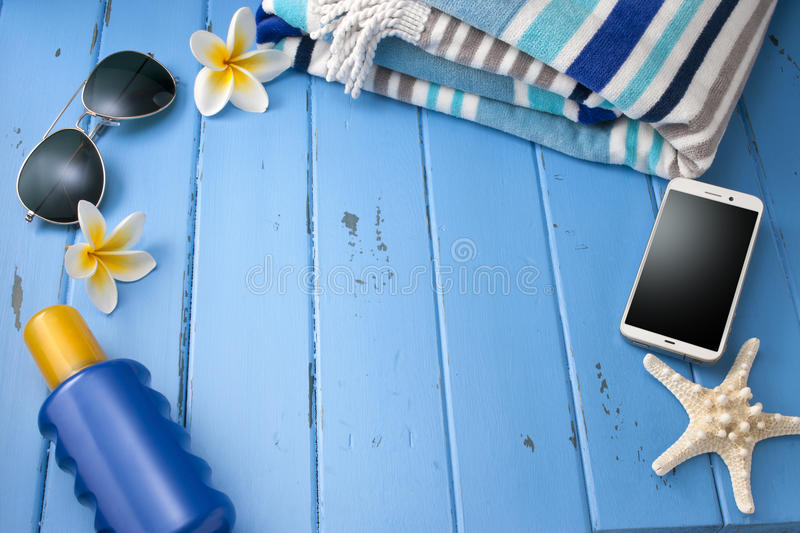 Vacation Tropical Travel Blue Background. A blue background with a tropical seaside theme including a cell phone, sunglasses, beach towel, sun cream