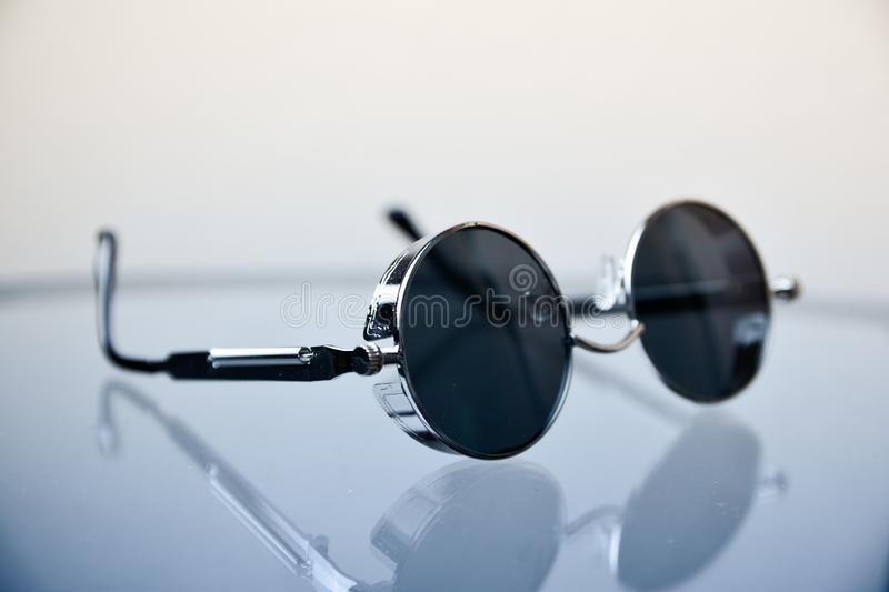 metal sunglasses on glass on a white background royalty free stock photos