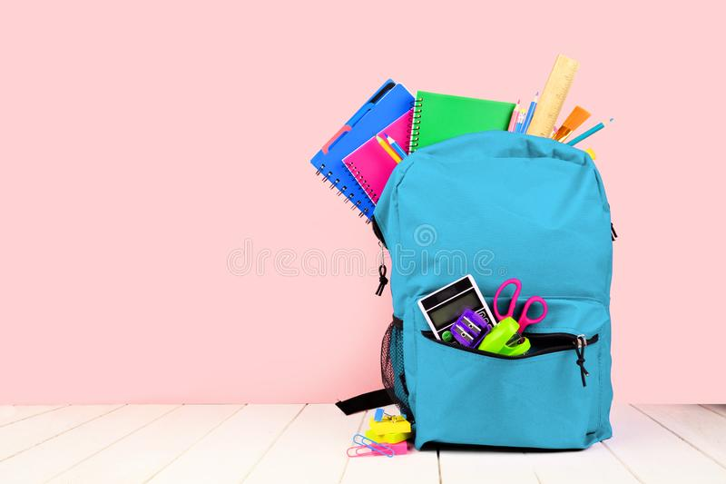 Blue backpack full of school supplies against a pink background. Back to school. stock image