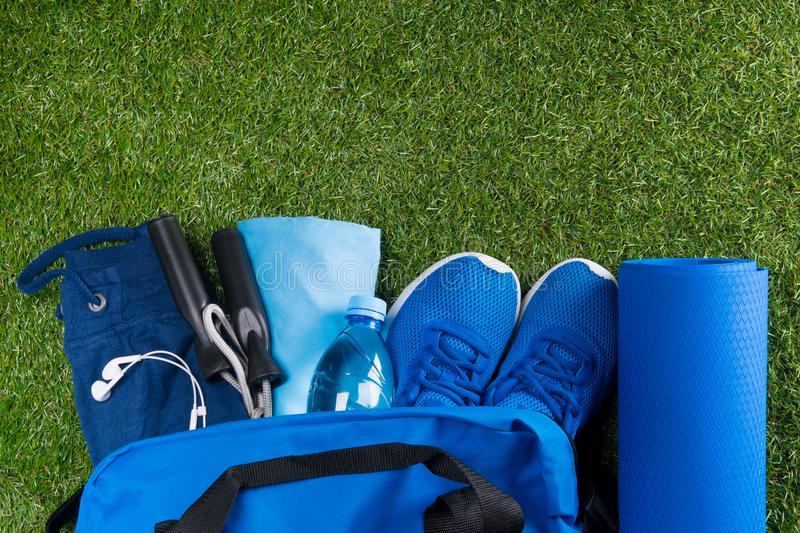 Blue bag on the green grass, with a set of sports things and shoes, water in the bottle and music for the mood stock photo