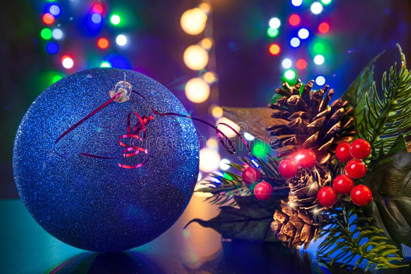 Blue ball and Christmas tree branch with bumps are on the shiny table/background.There are different colors light on the backgroun royalty free stock photos