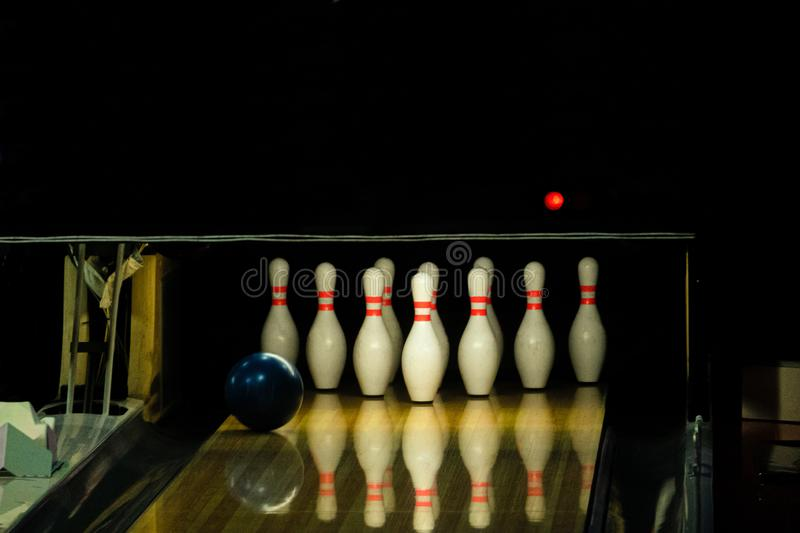 Blue ball rolling on a bowling alley lane with pins.  royalty free stock images