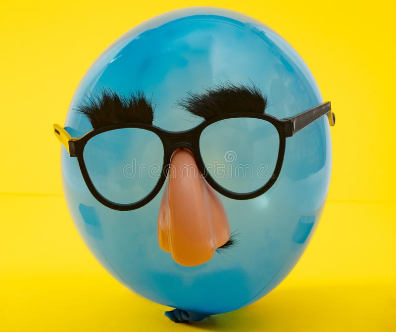 Blue Ballon with funny mask stock image