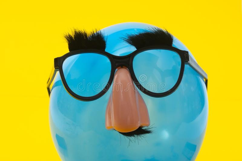 Blue Ballon with funny mask royalty free stock images