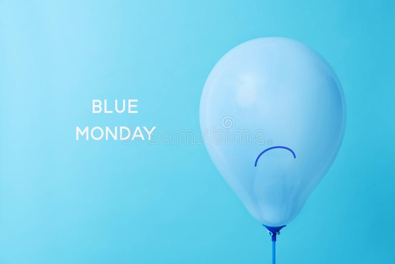 Blue balloon with a sad face and text blue monday stock photo