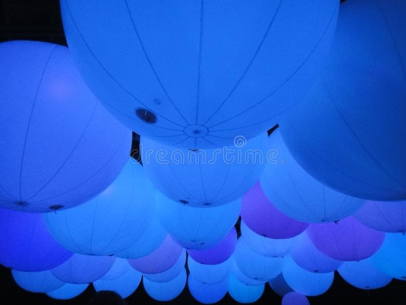 Blue balloons floating in a dark room to calm mood royalty free stock photo