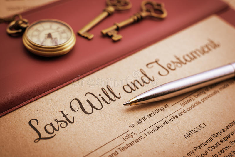 Blue ballpoint pen, antique pocket watch, two brass keys and a last will and testament on a vinyl desk pad. stock images