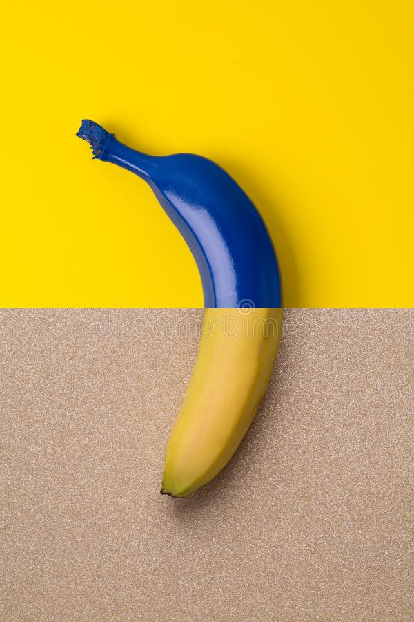Blue banana on the bright background of blue and gold colors stock photography