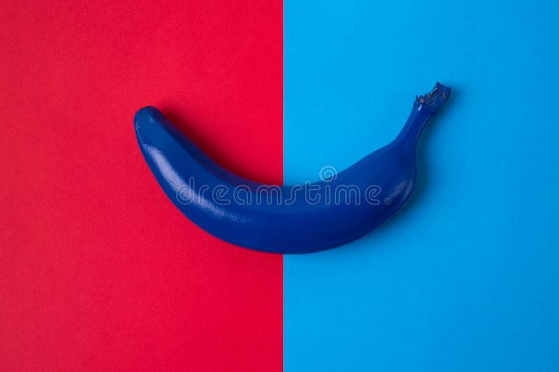 Blue banana on the bright background of red and blue colors. Top view image royalty free stock image