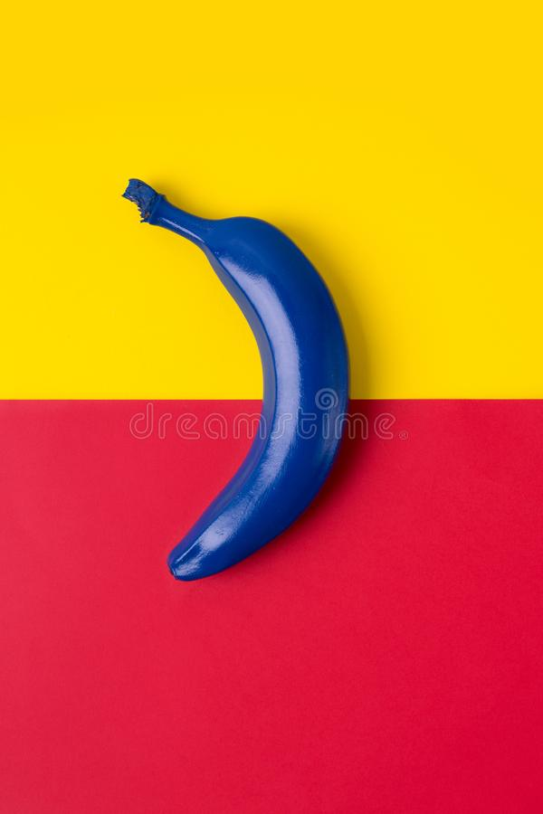 Blue banana on the bright background of red and yellow colors. Top view image royalty free stock image