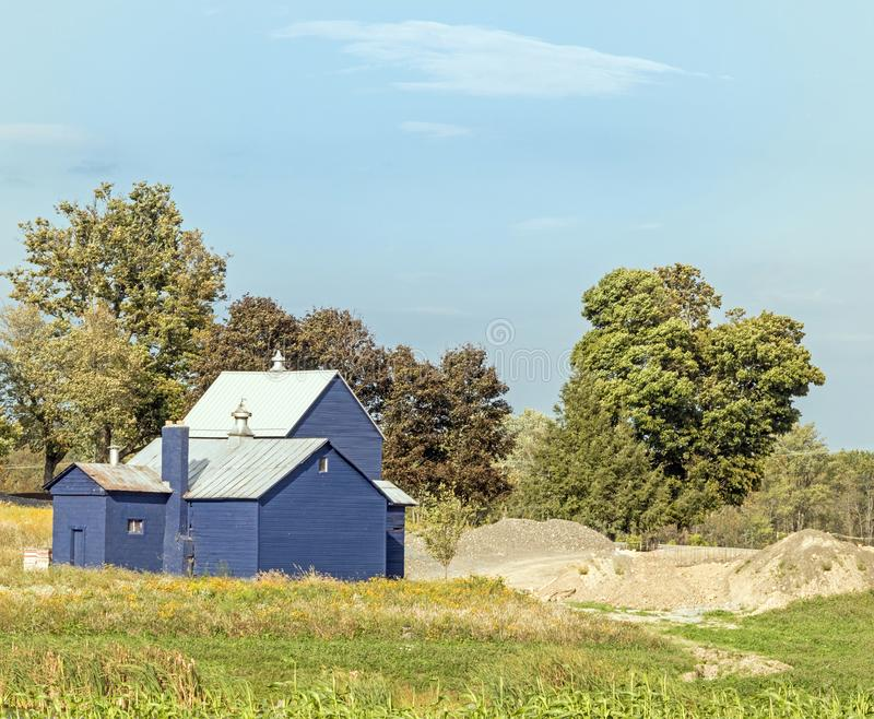Blue barn and storage with sand pile. In grass field with blue sky and white clouds, upstate rural New York, early Autumn royalty free stock photos