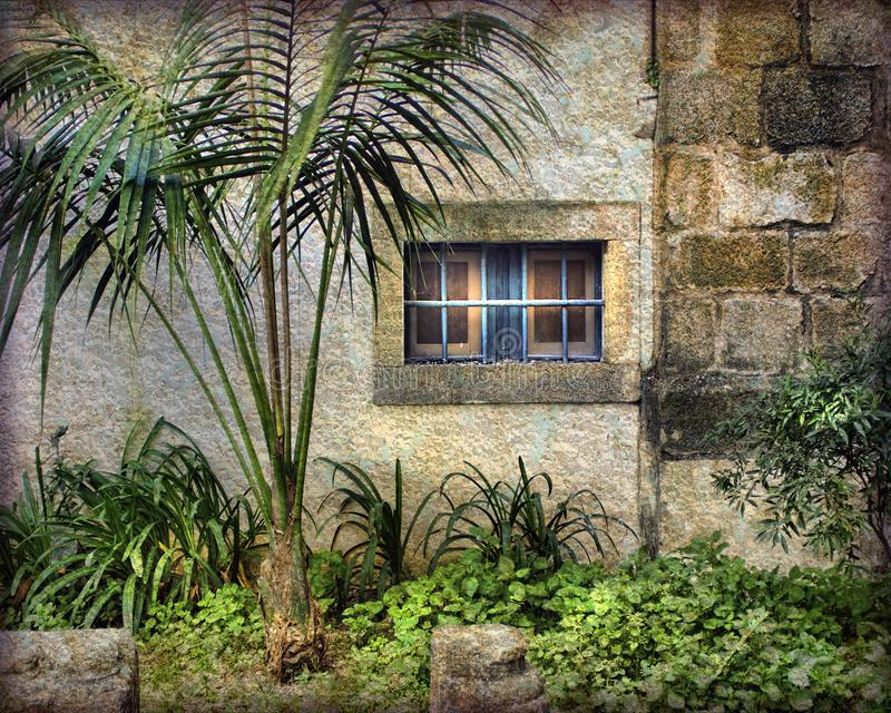 Blue Bars, Painterly and Textured, in Portugal. Blue bars guard a window set deep in a wall. Lush foliage is planted along the walls of Évora, Portugal. The royalty free stock photos